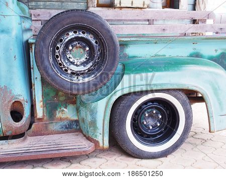 Spare tyre on vintage green truck in the garage
