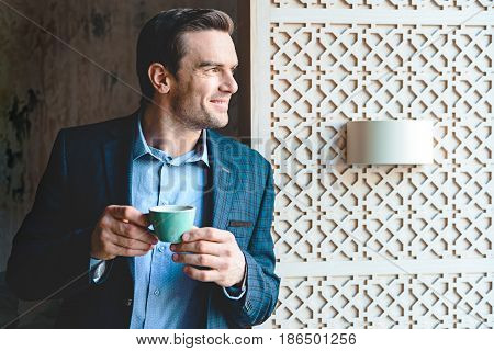 happy bristled male tasting cup of delicious coffee while looking away