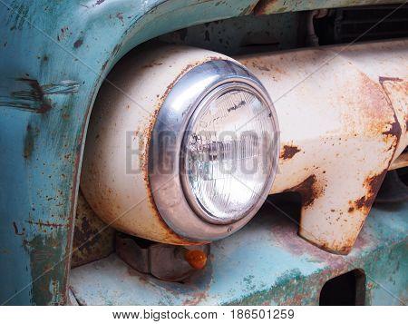 Close up retro headlight on vintage old car.
