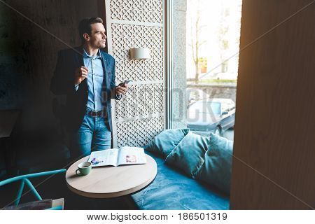 Man expressing thoughtfulness while watching at window in comfortable apartment. He is using phone