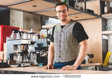 Portrait of friendly stubbled barista is locating in cozy kitchen. Different equipment situating near him in confectionary shop