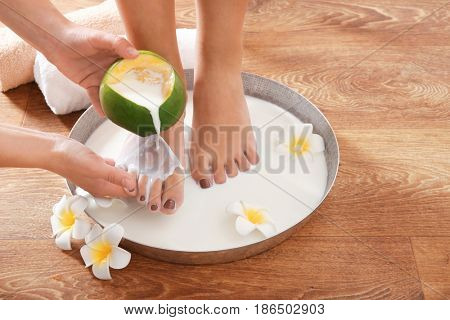Woman having spa treatments for feet in bowl with milk and flowers