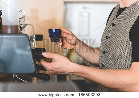 Close up man hands preparing cup of delicious coffee with special equipment in confectionary shop