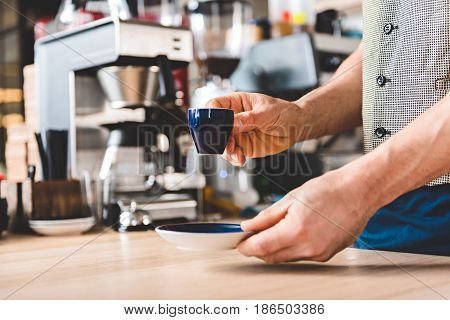 Close up hand of man serving cup of delicious coffee on desk in confectionary shop