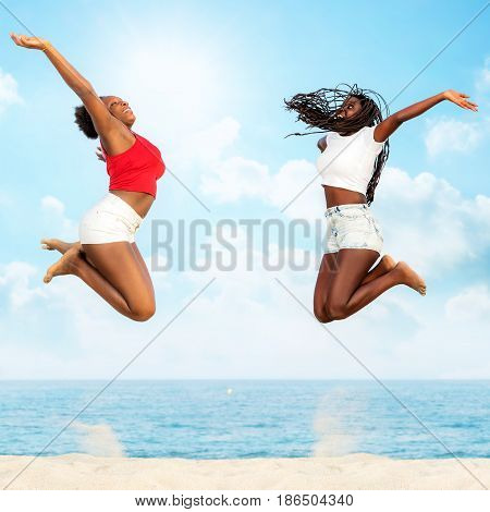 Full length action portrait of two african girlfriends jumping together on beach. Girls screaming with hands in air.