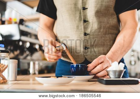 Close up hand of bartender putting cinnamon stick in cup of hot beverage in confectionary shop