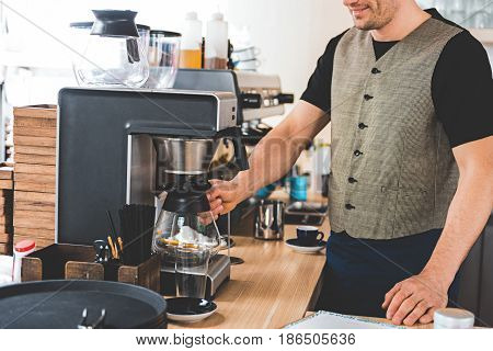 Happy bristled barista preparing mug of appetizing coffee with special equipment in candy store