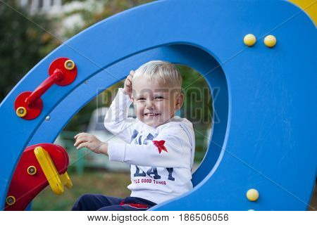 Blonde Little boy playing on the playground, summer outdoors