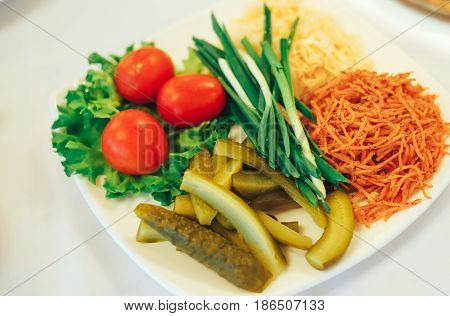 a dish of pickles marinated cucumbers tomatoes cabbage, Korean lettuce, and green onions