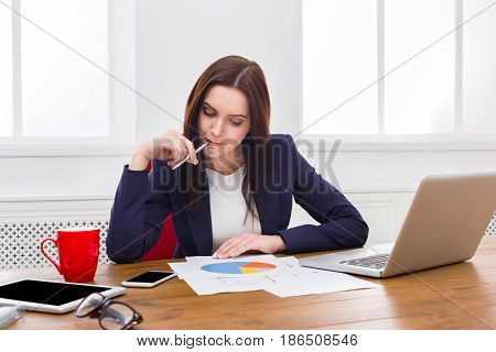 Paperwork. Business woman in office reading report document. Concentrated female manager working on marketing strategy at workplace