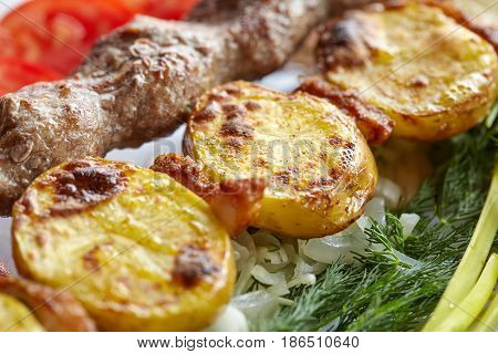 Grilled barbecue Lula Kebab with minced meat potatoes fresh vegetables and greens