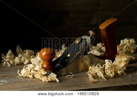 Woodworking hand planer tool on wooden boards in carpenter's workshop against dark brown background with copy space