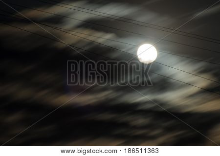 Full shiny moon caught in six strings cables partially covered with moving blurred clouds