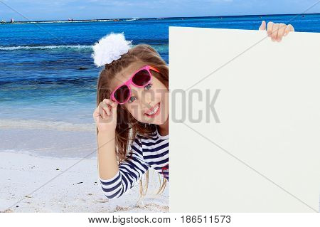 The little blonde girl with long hair and with a white bow on her head , in a blue striped summer dress.The girl in the dark sunglasses peeking from behind the banner.White sand , blue sea and blue sky.