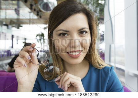 Portrait of a happy young girl who is sitting in a caf and holds glasses