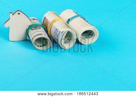 The concept of financial savings to buy a house. Mini model house dollars in rolls isolated on the blue background.