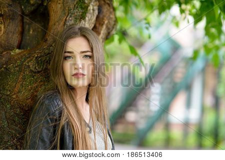 Young attractive woman hiding from the rain under a tree. Girl in rainy day, soft focus. Beautiful female face.