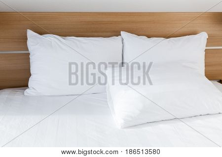 White Pillows Lay On Wide Empty Bed