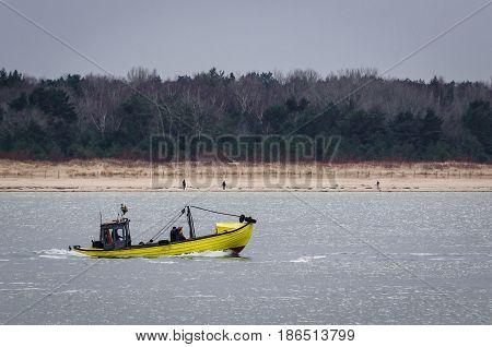 FISHING BOAT - The yellow boat sails near the sea shore