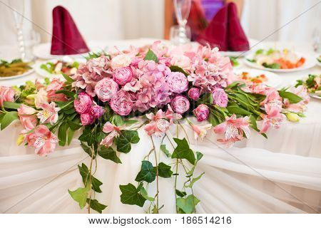 Pink bouquet of hydrangeas and peonies lies on the dinner table
