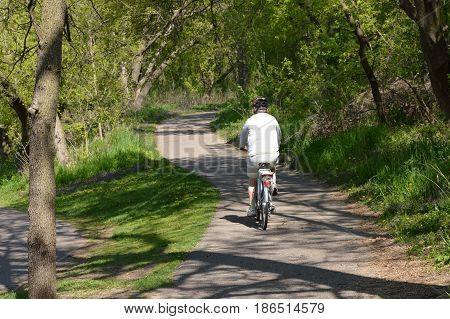 SAINT PAUL, MINNESOTA - MAY 2017: A middle age man biking on a bike path at a park in Saint Paul, MN.