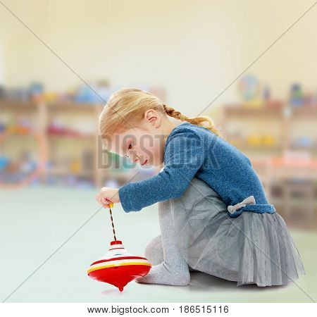 Pretty little blonde girl in blue blouse plays in humming top.In the Montessori room the children's garden where there are shelves with toys and material.
