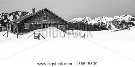 Romantic mountain hut in deep snow with mountains in background
