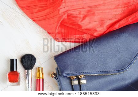 Woman's bag and it's content - nail polish, perfume in travel applicator, make-up brash, scarf