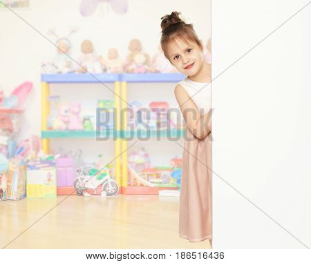 Cute little girl peeking out from behind the white banner.In the children's room.
