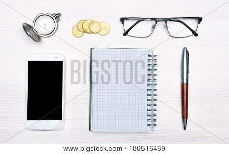 Spiral notebook with empty page wooden pen, white mobile phone, with blank screen, clock money and glasses on white wooden table background. Business man set concept.