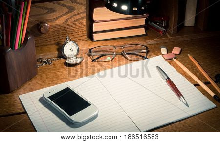 Education concept - notebook on the wooden table pen and colorful pencils book clock stapler mobile phone and black lamp on top.
