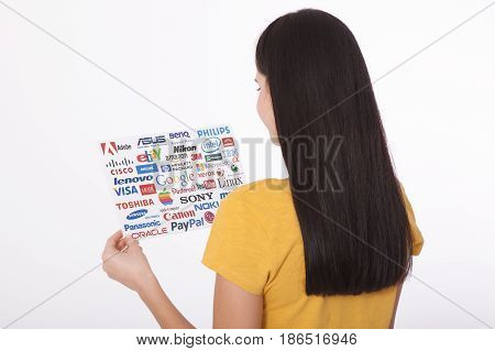 KIEV, UKRAINE - AUGUST 22, 2016: Woman hands holding collection of inscriptions, symbols of popular social media:Twitter, Google, Instagram, Pinterest, YouTube, Linkedin and others printed on paper scattered randomly.