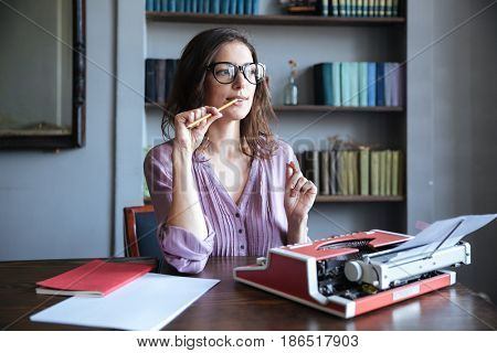 Portrait of a pensive mature authoress in glasses sitting at the table with papers and typewriter and looking away
