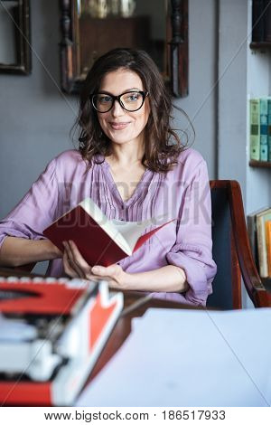 Portrait of a smiling mature authoress in eyeglasses sitting at the table and holding notebook indoors