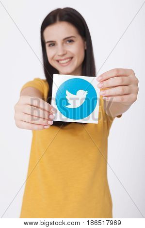 KIEV, UKRAINE - AUGUST 22, 2016: Woman hands holding Twitter logotype icoi bird printed paper close up. Twitter is an online social networking service that enables users to send and read short messages.