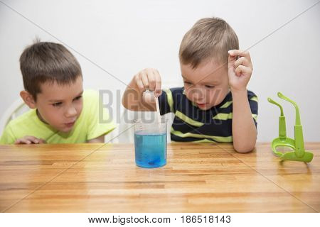 Children enthusiastically watching chemistry experiment. Boy added to the water blue dye