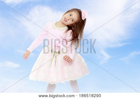 Dressy little girl long blonde hair, beautiful pink dress and a rose in her hair.She tipped to the side of the head.On the background of summer blue sky and fluffy clouds.