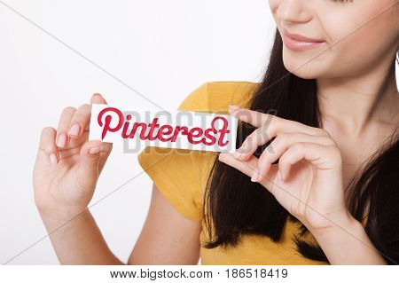 KIEV, UKRAINE - AUGUST 22, 2016: Woman hands holding Pinterest ilogotype icon printed paper close up. Is photo sharing website.