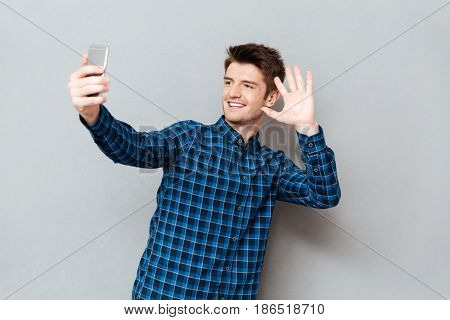 Young man greeting with somebody while making video call or selfie on smartphone