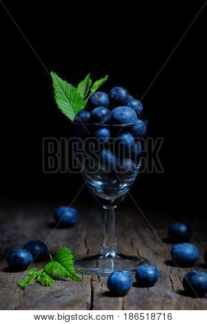 Blueberries with leaves in small glass