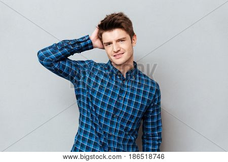 Young man holding hand near head posing at camera isolated