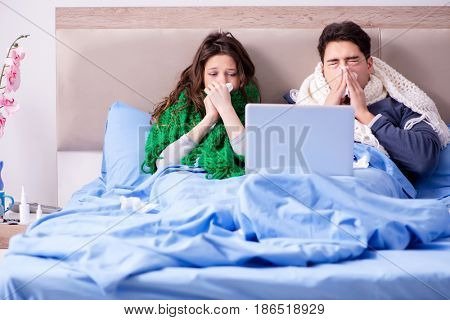 Sick wife and husband in bed with laptop