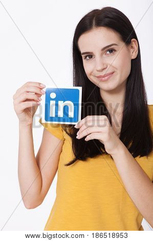 KIEV, UKRAINE - August 22, 2016: Woman hands holding Linkedin icon sign printed on paper on white background. Linkedin is a business social networking service.