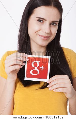 Kiev, Ukraine - August 22, 2016: Woman hands holding colorful Google plus icon printed on paper on grey background.Google is USA multinational corporation.