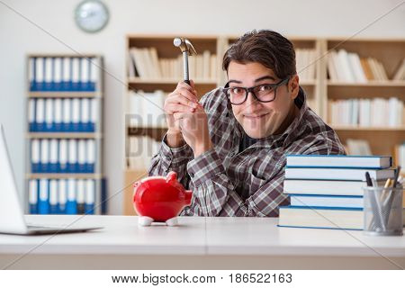 Young student breaking piggy bank to buy textbooks