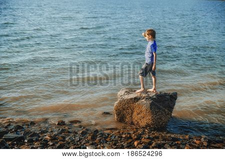 boy standing on the beach. kid stands on a rock by the sea and looks into the distance. Copy space for your text