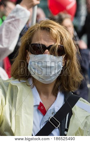 BERLIN - MAY 01 2016: Woman in a medical mask. Members of trade unions workers and employees at the demonstration on the occasion of Labour day.