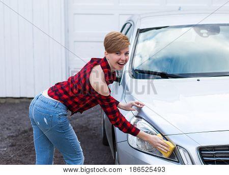 Women is washing a car. Women with short hair clean a car