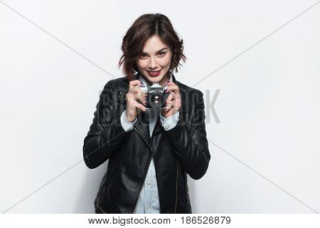 Young female in black leather coat posing with retro photo camera in hands and looking at camera.