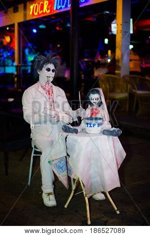 Pattaya Thailand May 19 2013: A man and a doll in white clothes in blood on Wolking Street.